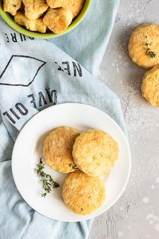 白いセラミックプレートにチーズとタイムのおいしいスコーンまたはクッキー。