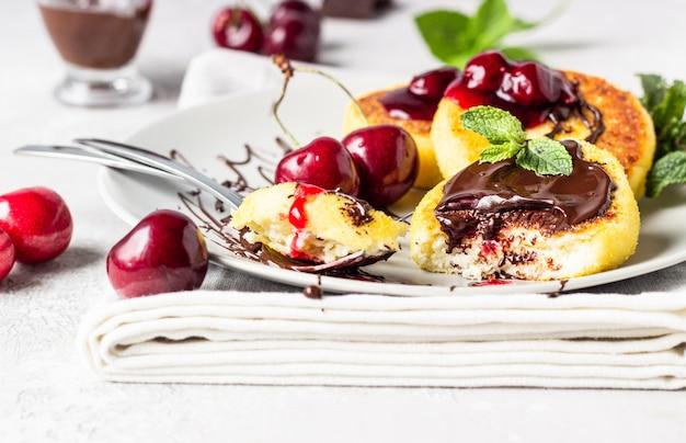 チョコレートとチェリージャム、新鮮なチェリーとミントのカッテージチーズのパンケーキ。伝統的なウクライナ料理とロシア料理。シルニキ。健康とダイエットの朝食。