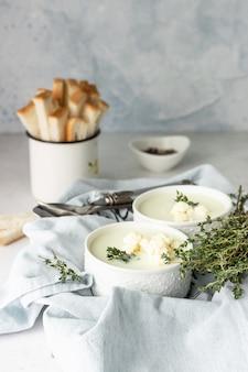 白いセラミックボウルにカリフラワーのクリームスープを添え、新鮮なカリフラワー、タイム、パンを添えます。秋または冬の快適な食事。