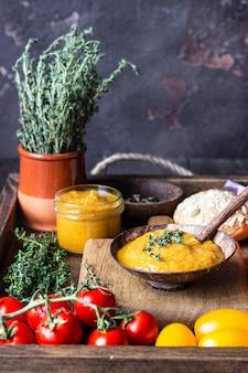 Овощная икра в банках, свежие помидоры, лук, морковь, баклажаны и тимьян подаются с хлебом в деревянном подносе.