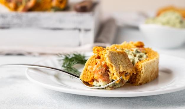 クリームチーズ、アボカド、サーモンの風味豊かなカボチャまたはニンジンロール。無グルテンの。
