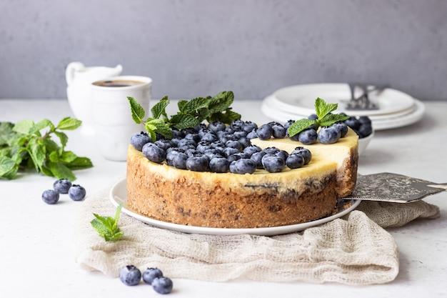 ニューヨーク風チーズケーキ、ブルーベリー、ミントの白いプレート。