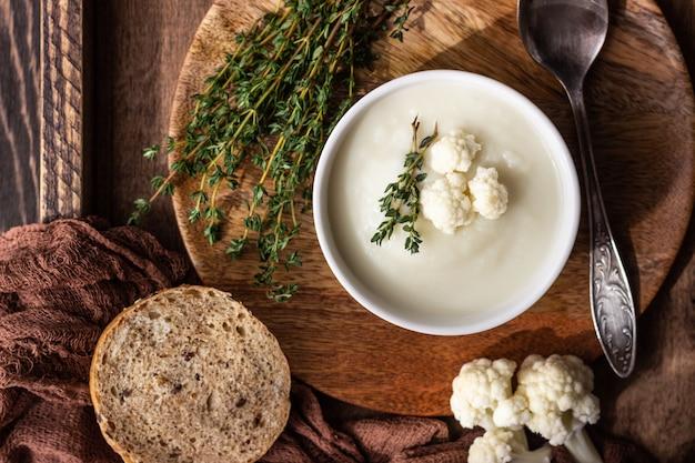 白いセラミックボウルにカリフラワーのクリームスープを添え、新鮮なカリフラワー、タイム、パンを添えます。