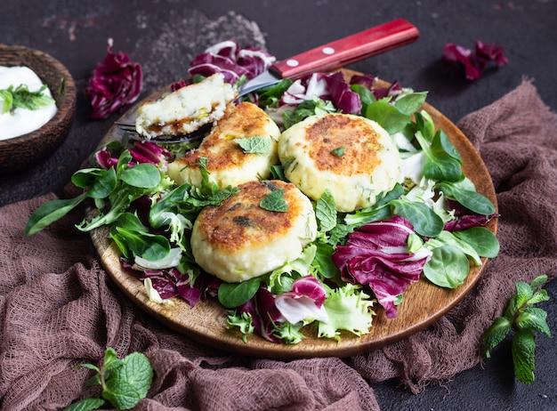 チーズとハーブ入りのカッテージチーズのパンケーキにサラダミックスとサワークリームを添えて。