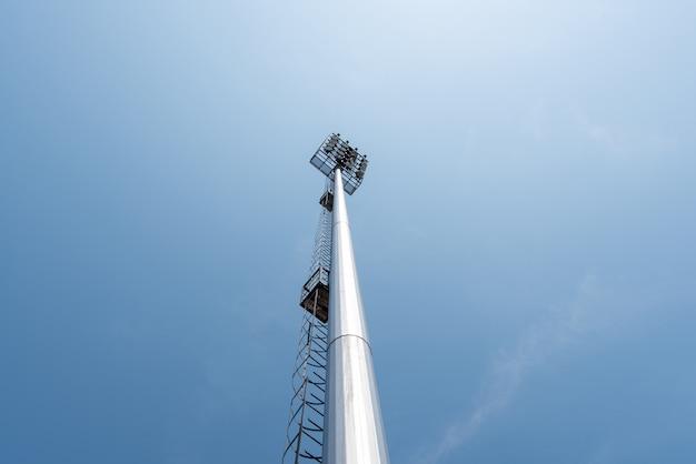 青い空のスポーツアリーナのライトポールタワー