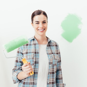若い女性が彼女の家を塗る