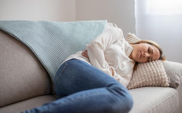 Девушка с болит живот, сидя на диване