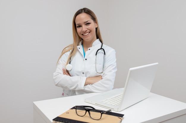自信を持って医師がオフィスで腕を組んで座っています。
