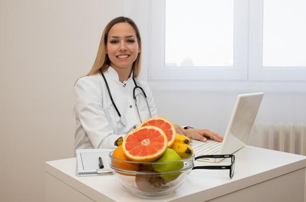 Усмехаясь диетолог в ее офисе, здравоохранении и концепции диеты