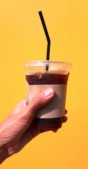 カップに水をまく、コーヒーカップを持っている手