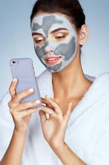 彼女の顔に粘土のマスクを持つきれいな女性