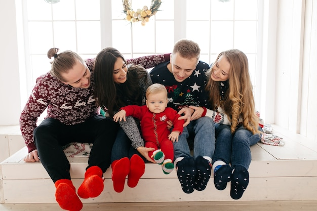 クリスマスツリーの背景に贈り物とスタジオで幸せな笑顔の家族