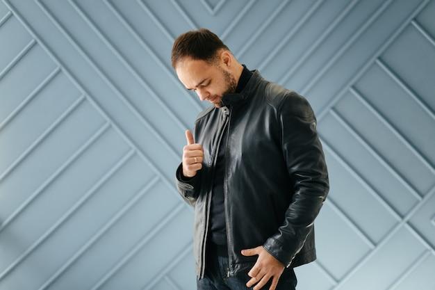 古典的な黒の衣装でエレガントな若いハンサムな男。スタジオファッションのポートレート。