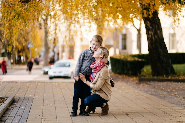 秋に屋外を歩く息子と母親