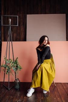 Портрет потрясающей модной женщины, сидящей в кресле