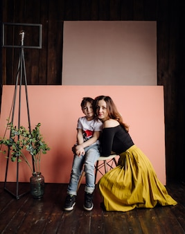 母と彼女の息子はスタジオでポーズをとって、カジュアルな服を着ています。