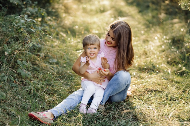 森で彼女のかわいい赤ちゃんを持つ若い母親