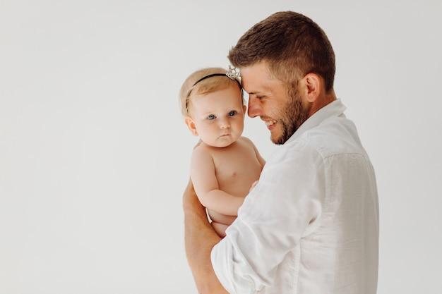 彼の腕の中で美しい小さな赤ちゃんを持つ若い父親