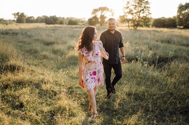 Молодая влюбленная пара гуляет в парке
