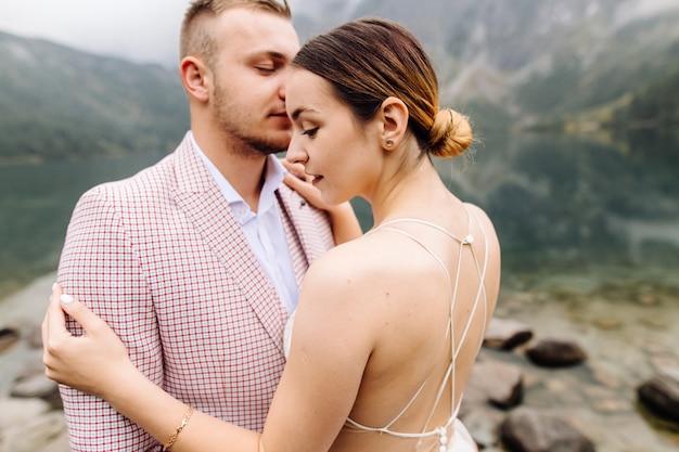 Романтическая свадьба пара в любви стоя на берегу моря глаз в польше. татры.