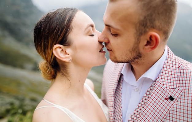 ポーランドのシーアイ湖の愛立っているロマンチックな結婚式のカップル。タトラ山脈。