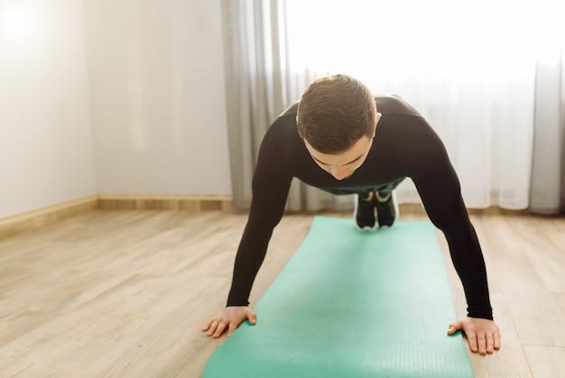 若い男が自宅でスポーツ演習を行う