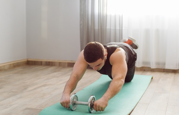 Молодой человек делает спортивные упражнения дома