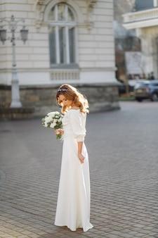 Красивая молодая женщина в свадебном платье позирует на улице в городе