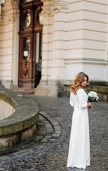 街の通りでポーズのウェディングドレスの美しい若い女性