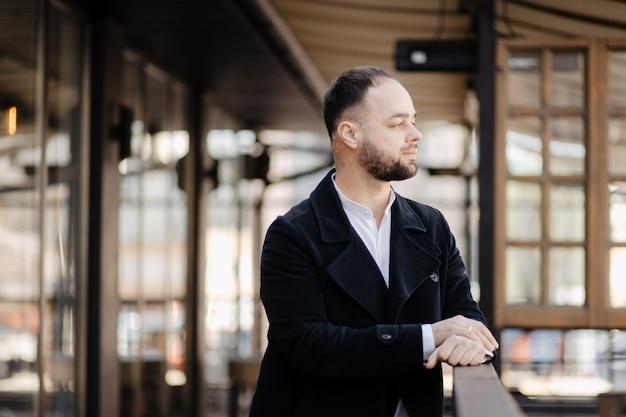 Портрет модного хорошо одетого человека с бородой, создавая на открытом воздухе