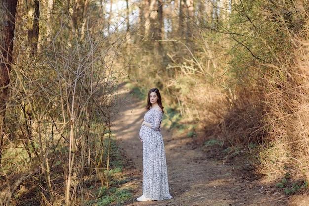 Молодая беременная женщина расслабляющий в парке на открытом воздухе