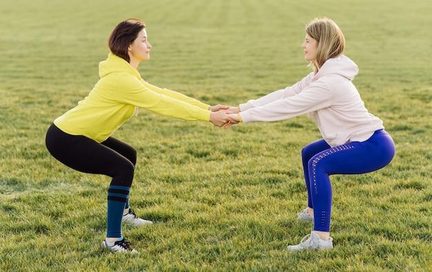 Молодые спортивные женщины на открытом воздухе делают упражнения