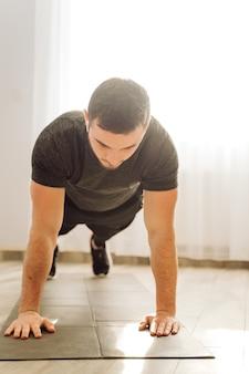Молодой человек делает фитнес упражнения дома