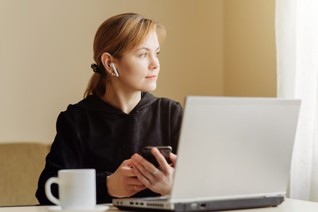 Женщина, используя ноутбук и мобильный телефон для его удаленной работы на дому