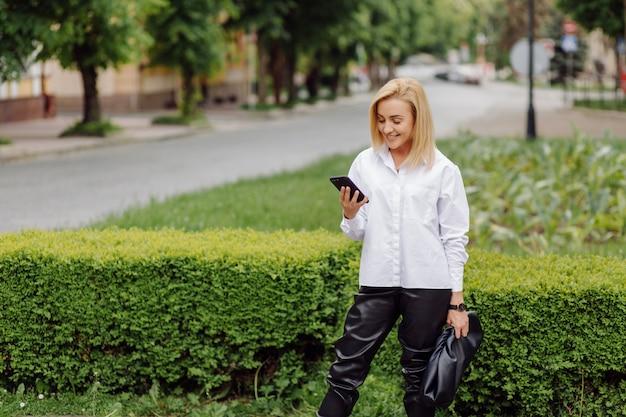 Счастливая молодая красивая женщина используя ее умный телефон гуляя на улицу города