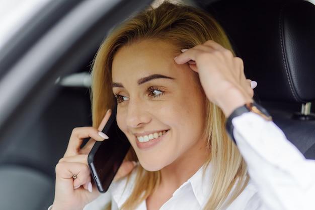 電話が付いている車の中の若い美しいブロンド
