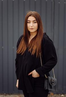 Красивая дружелюбная молодая женщина с коричневыми волосами до плеч, позирует на улице