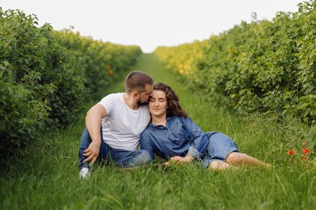 草の上に座ってリラックスした若いカップル