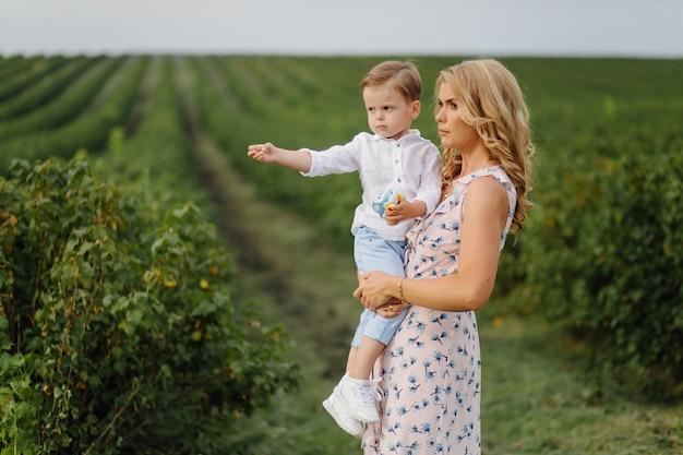 幸せな金髪の女性と夏の庭に立っているかわいい男の子