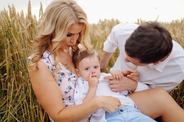 Счастливая молодая семья папа, мама и маленький сын выглядят счастливыми в парке