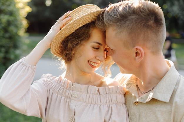 Молодая пара в любви на открытом воздухе. потрясающий чувственный открытый портрет молодой стильной модной пары позирует летом в поле