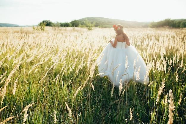花嫁は庭の中でポーズを取る美しいロングドレスを着ている。