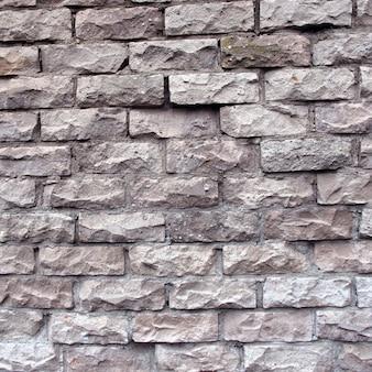 割れた白いレンガからのレンガの壁