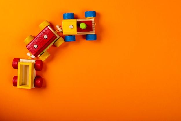 テキスト用のスペースとオレンジ色の背景に木製の電車。