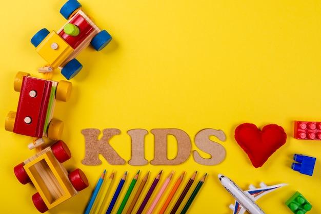 黄色の背景と様々な色鉛筆とテキストと子供と赤い布の心で書かれたカラフルな木製電車。