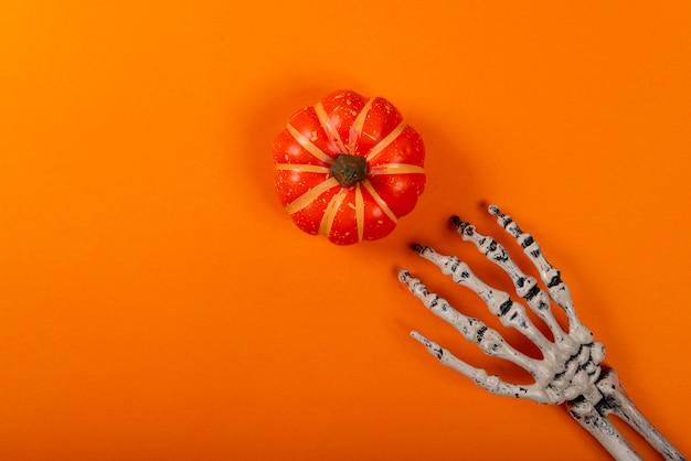オレンジ色のカボチャを引くスケルトン