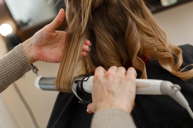 Профессиональный парикмахер, работающий с клиентом в салоне, мастер причесок делает вечернюю прическу