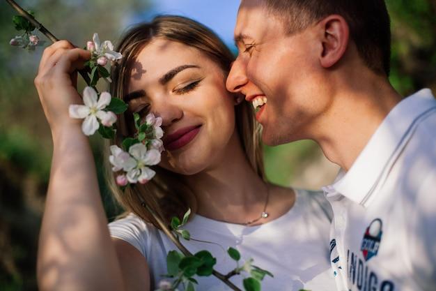 自然の中で愛情のある男と女のキス。愛の物語の屋外。春の公園で歩いている恋人たち。春の散歩にぴったりの愛のカップルの笑顔