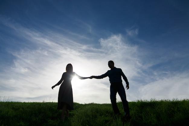 Силуэты влюбленных пар на природе в летнем вечере. молодой мужчина и женщина нежно обнимаются на закате