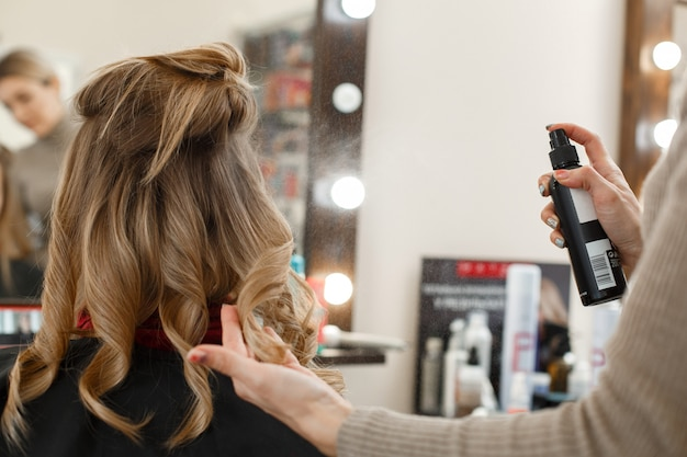 サロンで女性の髪をカットしてスタイリングするプロセス